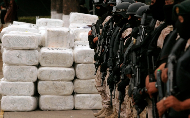 Soldiers stand guard next to narcotics wrapped in silver packages in Tijuana